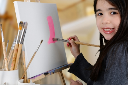 Girl painting a canvas while at school