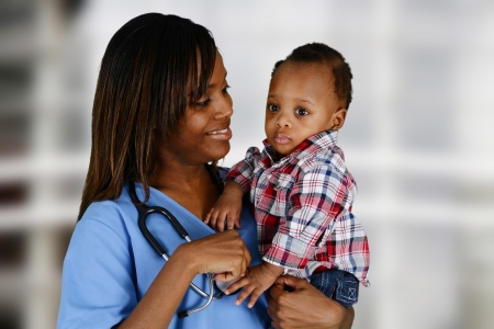 sick baby: Minority nurse working at her job in a hospital with baby Stock Photo