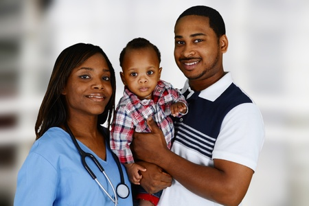 Minority nurse working at her job in a hospital with family photo