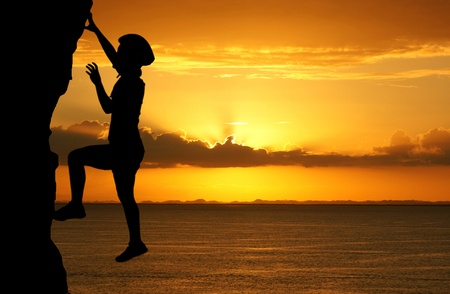 Girl climbing a tall mountain at sunset  photo