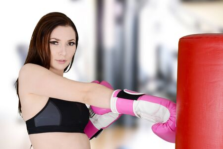 Woman kick boxing while at the gym photo