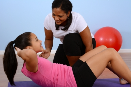 personal trainer: Teen girl working out in the gym Stock Photo