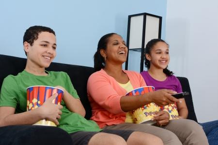 people watching tv: Familia que se sienta en el sof� viendo una pel�cula juntos