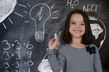 Girl at school standing at the chalk board Stock Photo