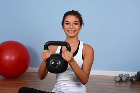 Teen girl working out while at the gym photo