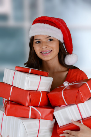 happy christmas: Happy teen girl smiling while holding christmas gifts Stock Photo