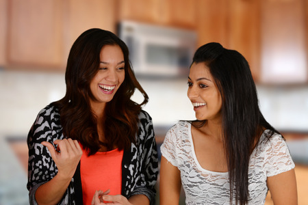women friends: Group of friends together in a kitchen Stock Photo
