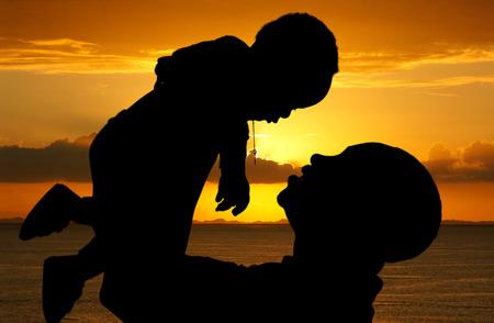 silueta niño: Padre y su hijo que juegan juntos al aire libre