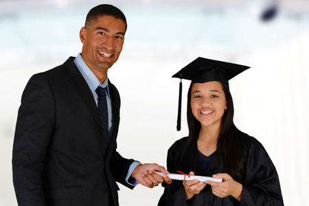 principal: Teacher at school with student who is graduating Stock Photo