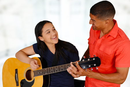 Teenage girl playing the guitar on a white background photo