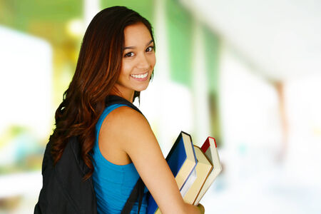 College student carrying her books at school photo