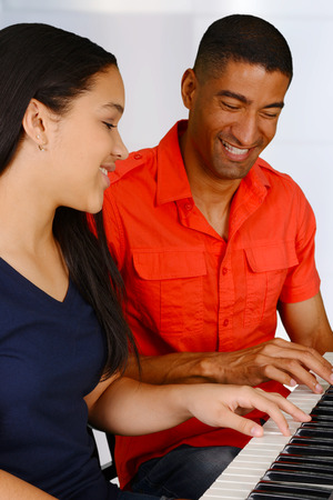 Teenage girl playing the piano with her teacher Stock Photo - 29088800