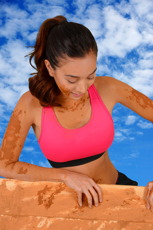 Woman competing in a mud run race photo