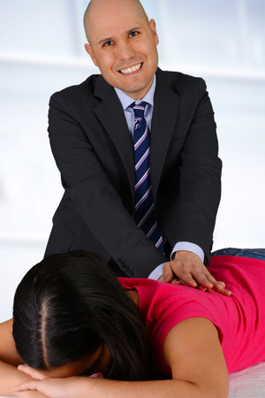 Pain Management: Male chiropractor working at his office with a patient