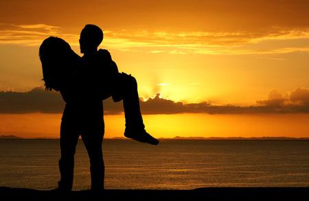 Een paar in liefde op het strand tijdens een zonsondergang Stockfoto