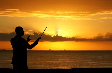 男性はビーチで、日没時に人々 を実施 写真素材