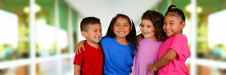 hispanic kids: Group of children standing in front of their school