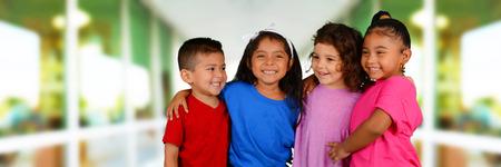 niños jugando: Grupo de niños de pie frente a su escuela Foto de archivo