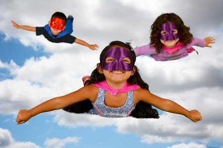 woman flying: Group of children who are dressed up as superheroes