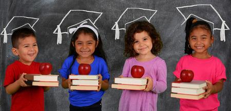 graduacion ni�os: Chico y chicas que sostienen los libros antes de la escuela joven