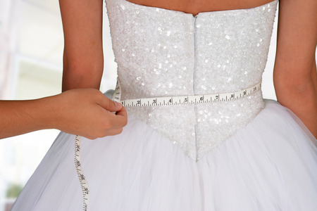 Woman in a wedding dress getting measured  스톡 콘텐츠