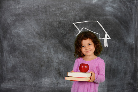 学校の前に彼女の本を持って若い女の子 写真素材