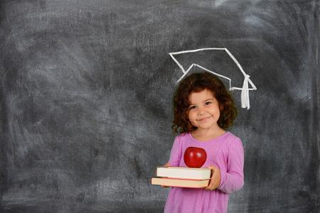 graduacion niños: Chica joven que sostiene sus libros antes de la escuela