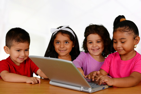 Group of children working on the computer at school photo