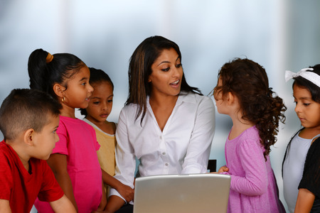 hispanic child: Group of children working on the computer at school