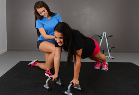 Woman working out while at the gym with a personal trainer Banque d'images