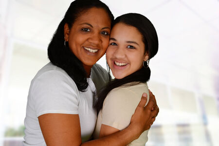 foster: Woman and daughter standing together in their home Stock Photo