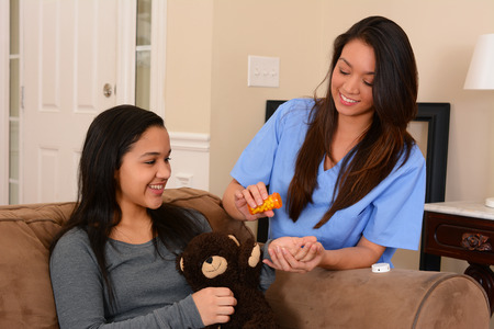 home health care: Home health care worker and a teen girl Stock Photo