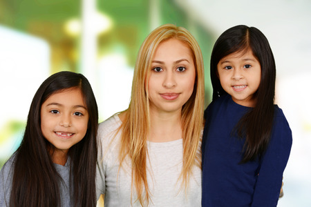 Mother and daughters together outside of their home Banco de Imagens