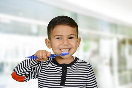 dientes sanos: Niño joven que está cepillando sus dientes Foto de archivo