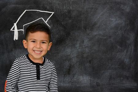 Happy little schoolboy posing in front of black chalkboard photo