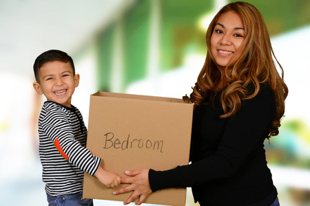 moving out: Mother and boy carrying moving box from bedroom
