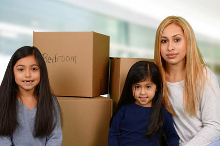 Mother and her two young daughters packed moving boxes Stock Photo