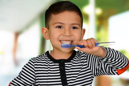 brown  eyed: Happy little brown eyed schoolboy brushing white teeth