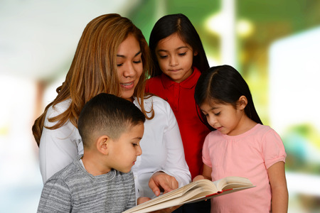 Blonde young latin mother reading to her three kids