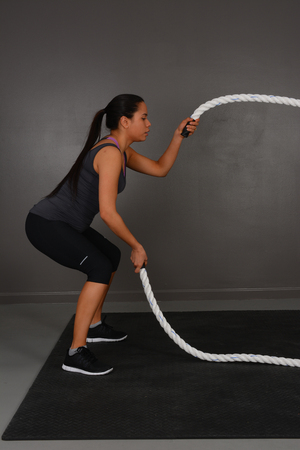 excercise: Young woman doing excercise indoors with rope