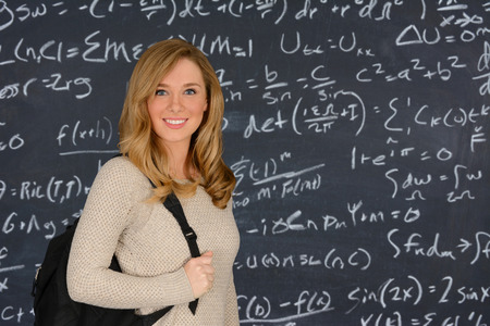 calculus: Happy blue eyed student girl standing in front of the blackboard