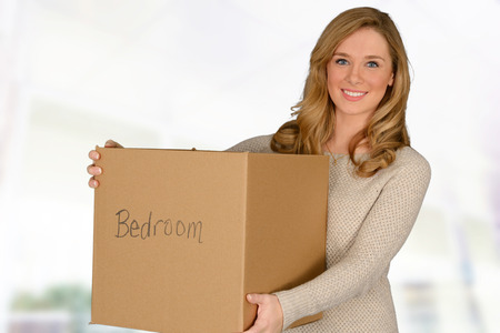 carrying: Happy young woman moving in carrying moving box
