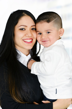 parental love: Young brunette mother holding her little son Stock Photo