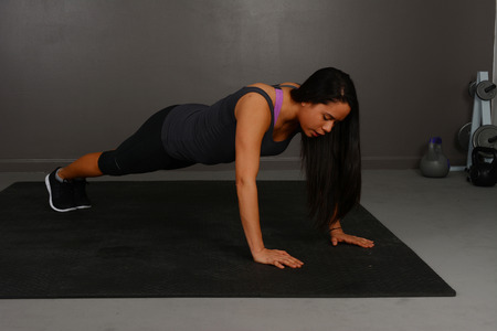 pushup: Female doing pushup workout in indoor gym
