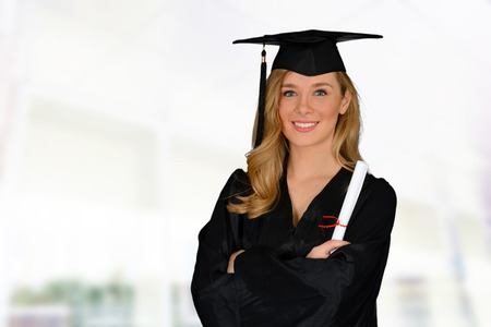 graduating: Young successful woman graduating from college holding a diploma