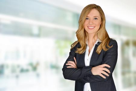 úspěšný: Mladá úspěšná žena s rukama zkříženýma pohledu na fotoaparát