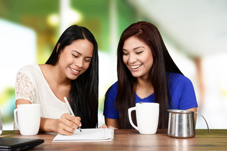 woman drinking tea: Two students who are studying for school together
