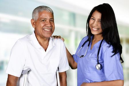 Health care worker helping an elderly man Фото со стока