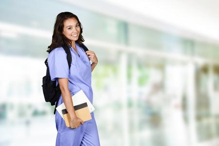 pielęgniarki: Kobieta pielęgniarka, która studiuje na swojej pracy Zdjęcie Seryjne