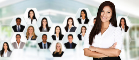hispanic americans: Businesswoman working in an office with her team